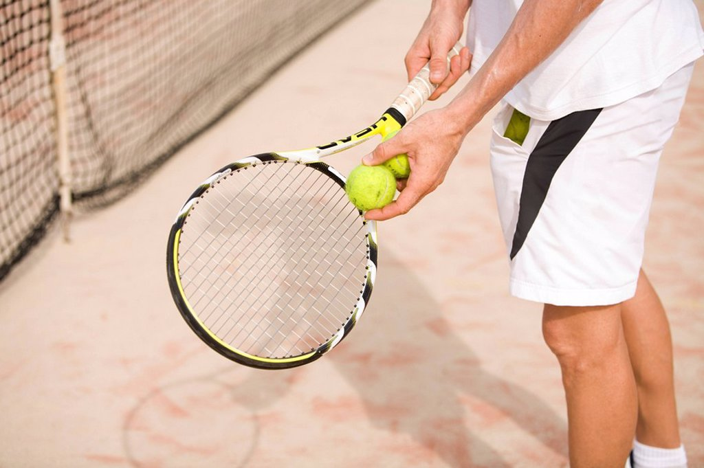 Stock Photo: 1815R-62221 Male tennis player holding tennis racket, low section