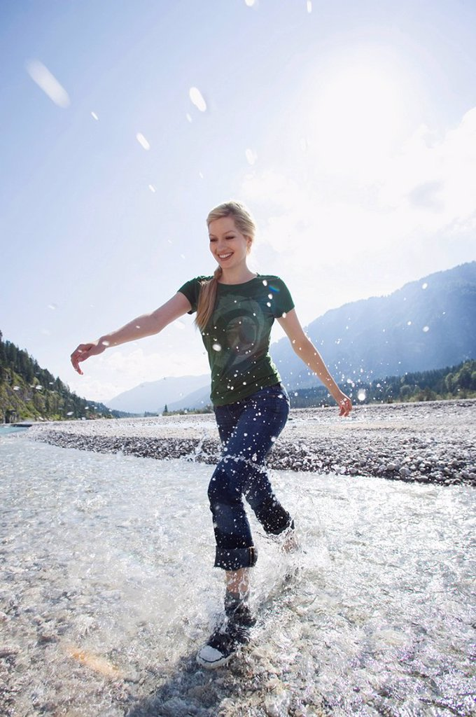 Germany, Bavaria, Tölzer Land, Young woman running through river, smiling : Stock Photo