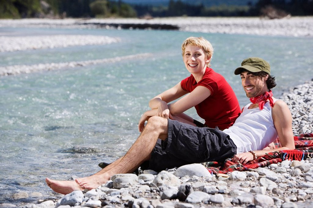 Germany, Bavaria, Tölzer Land, Young couple sitting on riverbank : Stock Photo