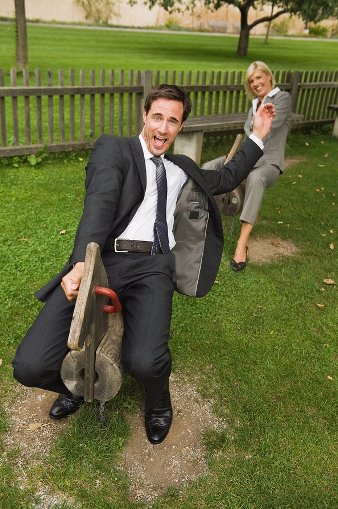Germany, business people riding rocking horses in playground : Stock Photo