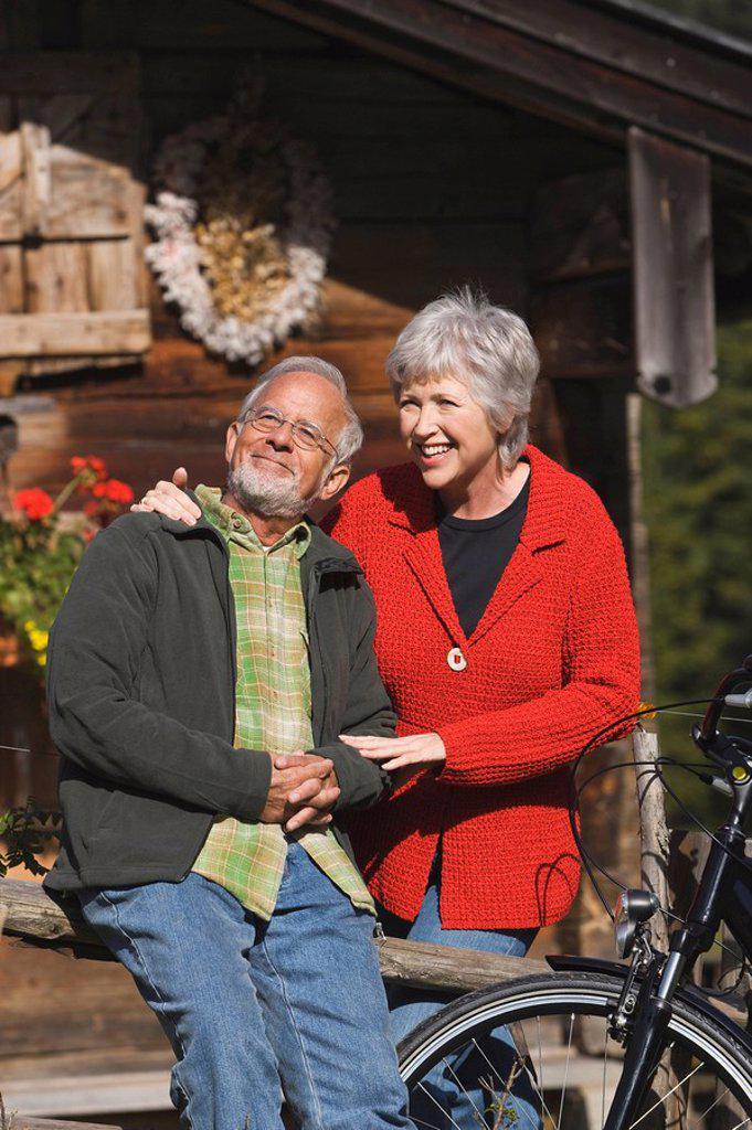 Austria, Karwendel, Senior couple in front of log cabin : Stock Photo
