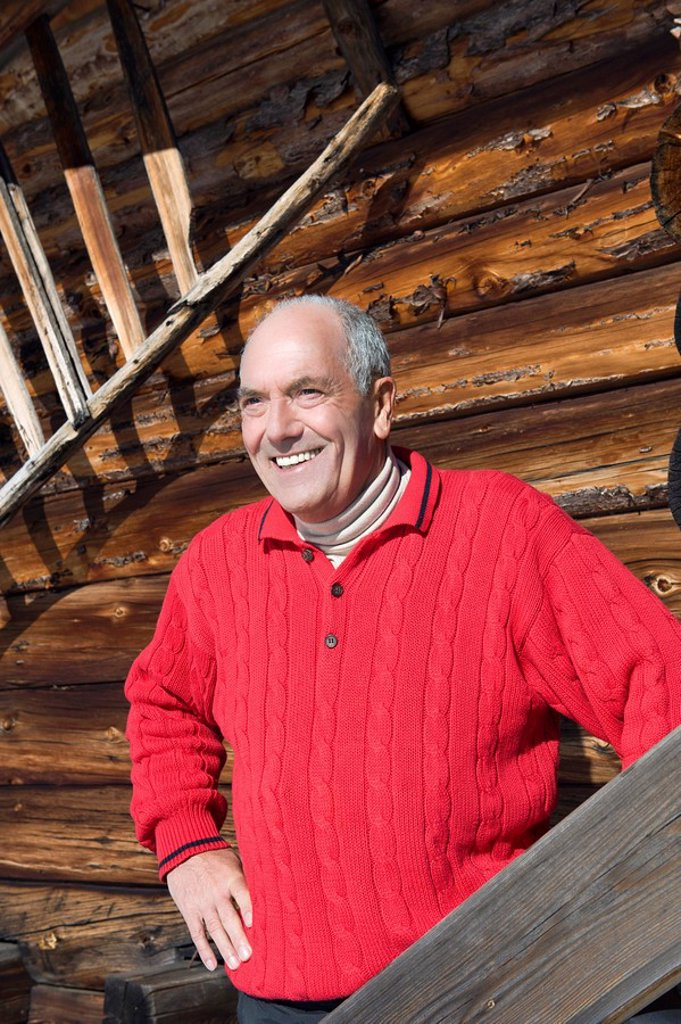 Stock Photo: 1815R-64132 Italy, South Tyrol, Seiseralm, Senior man standing in front of wooden wall, smiling, portrait