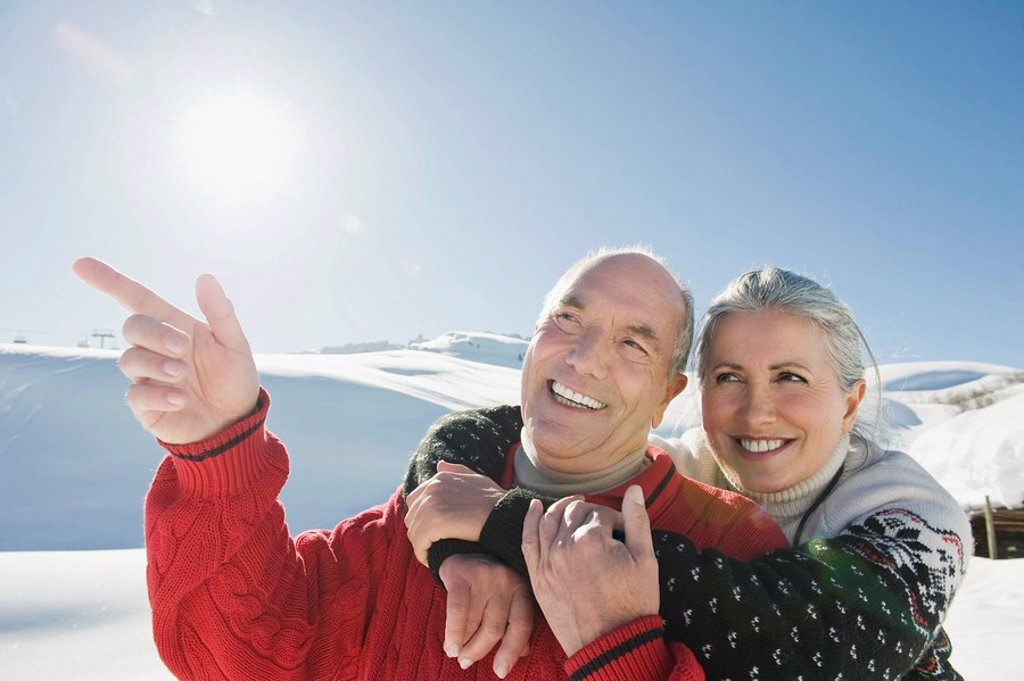 Italy, South Tyrol, Seiseralm, Senior couple in winter scenery, man pointing, portrait, close_up : Stock Photo