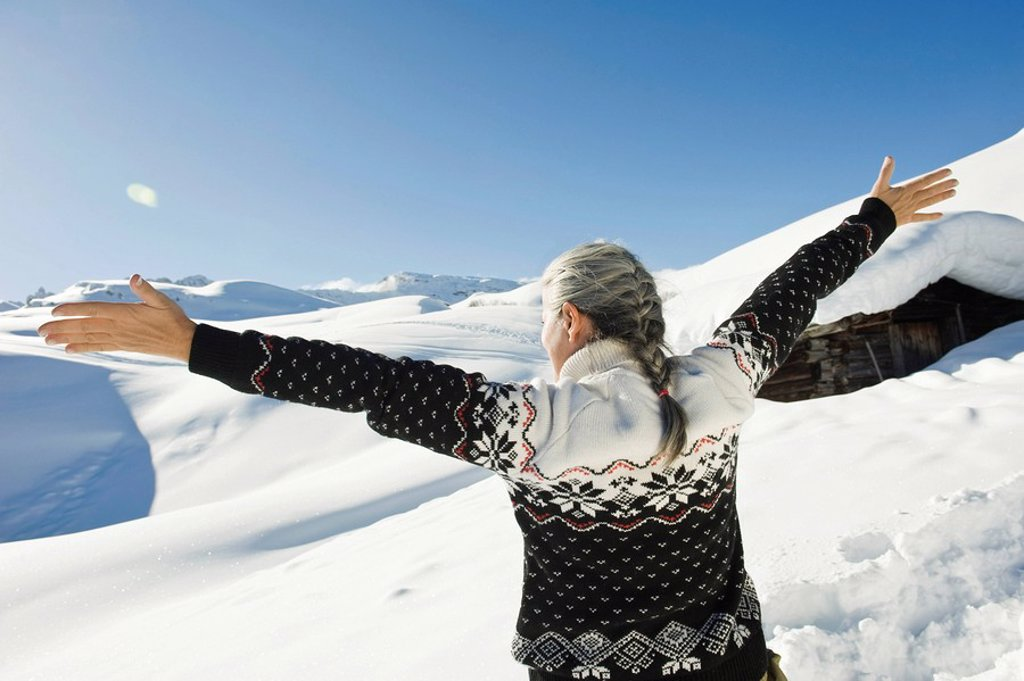 Italy, South Tyrol, Seiseralm, Senior woman, arms outstretched, rear view : Stock Photo