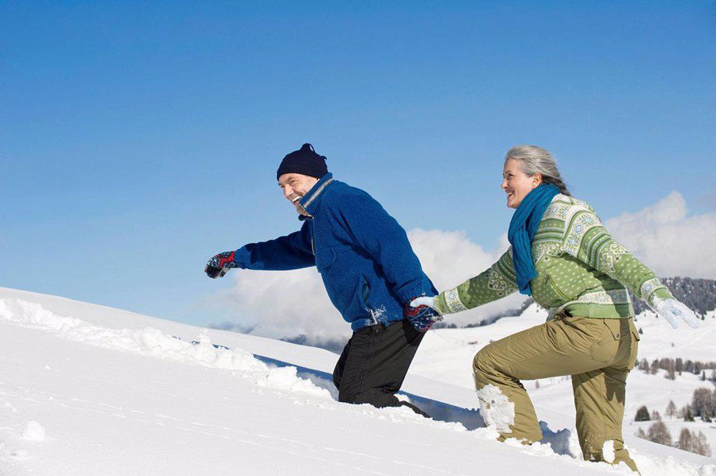 Italy, South Tyrol, Seiseralm, Senior couple walking in snow, side view, portrait : Stock Photo