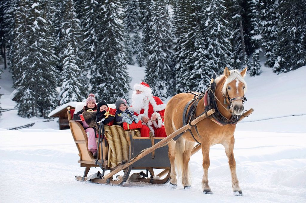 Italy, South Tyrol, Seiseralm, Santa Claus and children taking a sleigh ride : Stock Photo