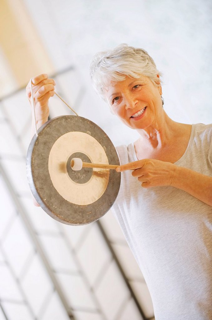 Stock Photo: 1815R-64877 Senior woman holding gong, portrait