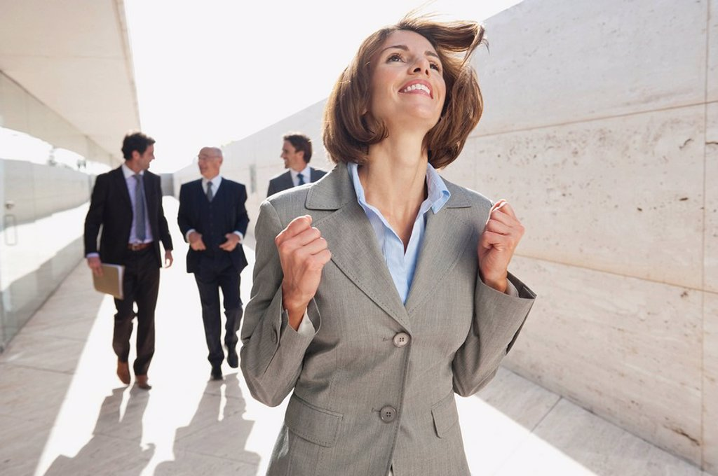 Spain, Mallorca, Business people walking together, Businesswoman in foreground cheering : Stock Photo