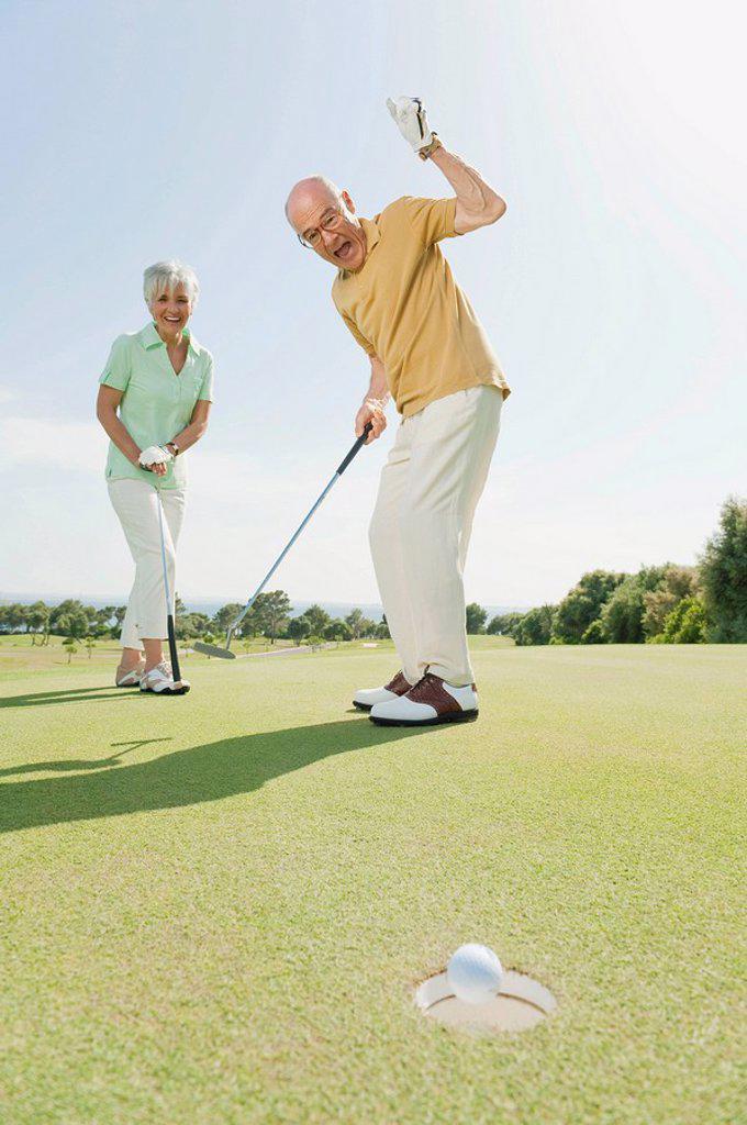 Stock Photo: 1815R-65203 Spain, Mallorca, Senior couple on golf course, man cheering
