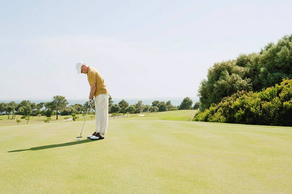 Spain, Mallorca, Senior man playing golf, side view : Stock Photo