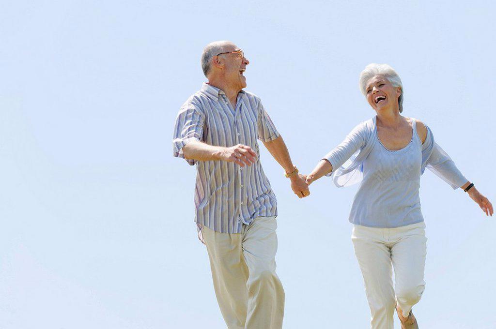 Senior couple running hand in hand, portrait : Stock Photo