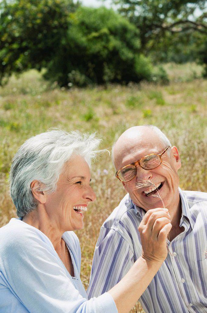 Spain, Mallorca, Senior couple sitting on grass, having fun, portrait : Stock Photo