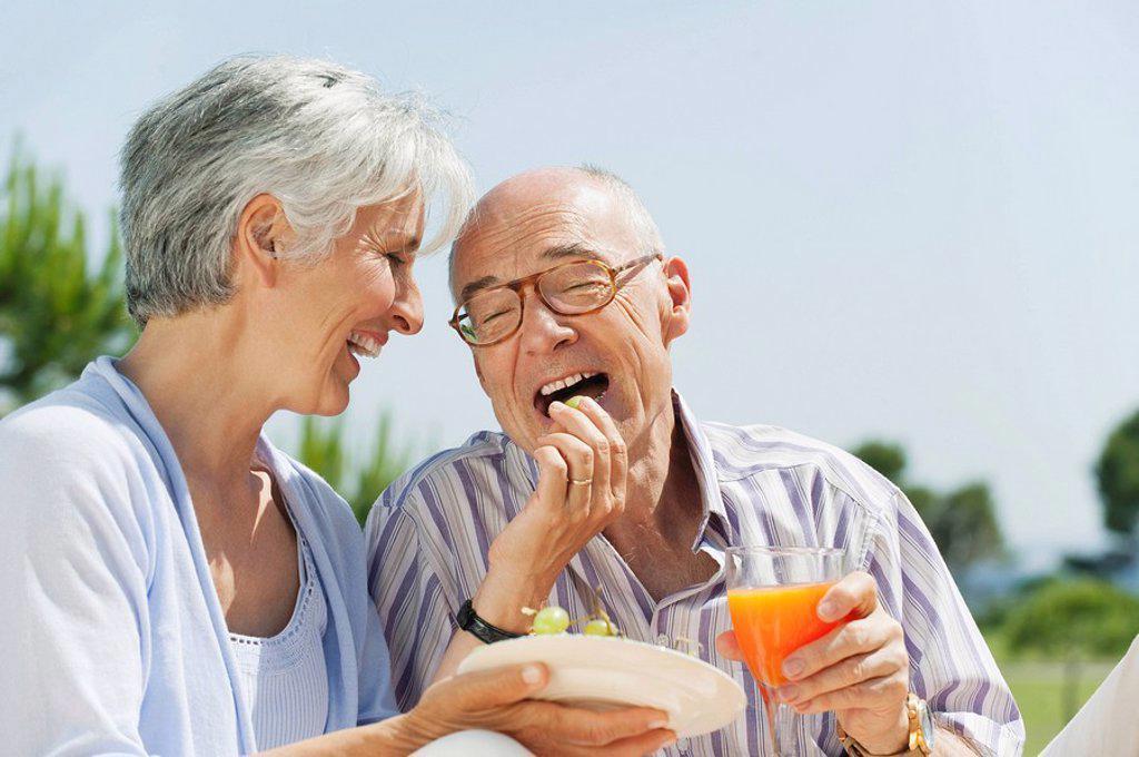 Stock Photo: 1815R-65298 Spain, Mallorca, Senior woman feeding grapes to senior man, laughing, portrait