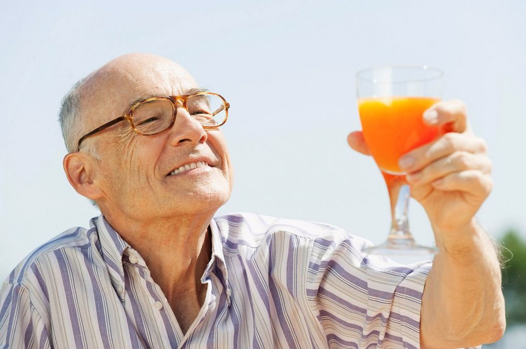 Stock Photo: 1815R-65303 Spain, Mallorca, Senior man holding glass with orange juice, portrait