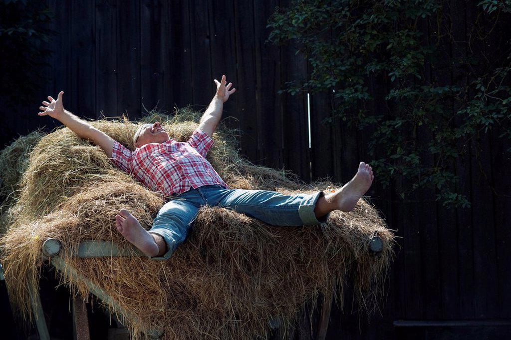 Germany, Bavaria, Senior man lying on haystack : Stock Photo