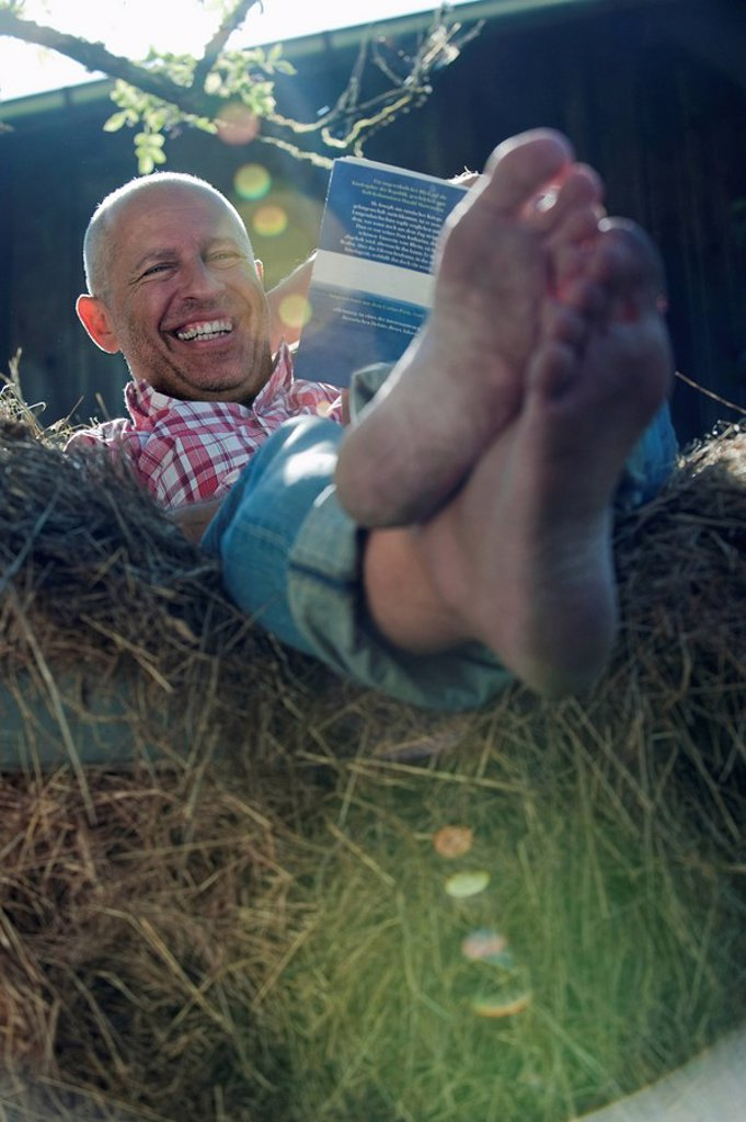 Germany, Bavaria, Senior man sitting on haystack, reading a book : Stock Photo