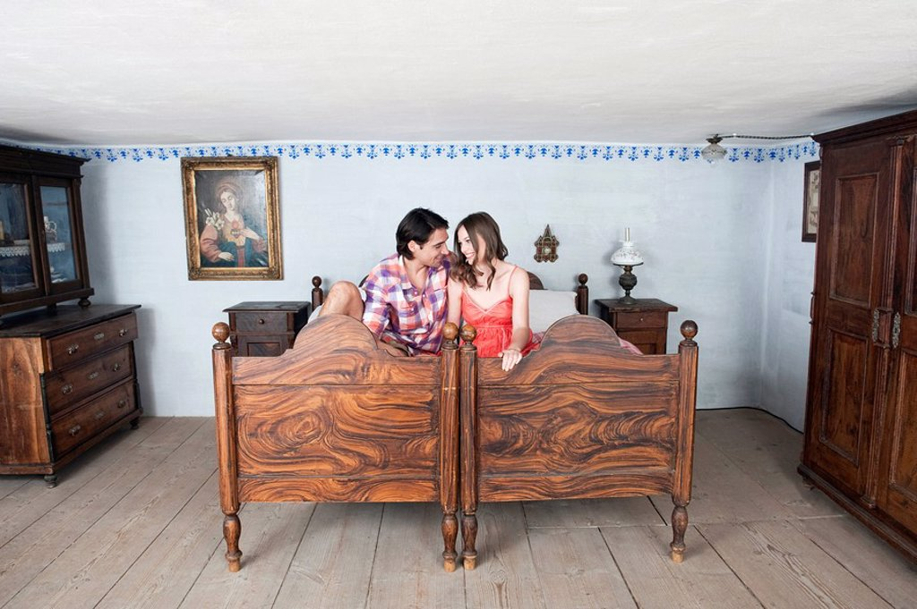Germany, Bavaria, Young couple in rural bedroom : Stock Photo