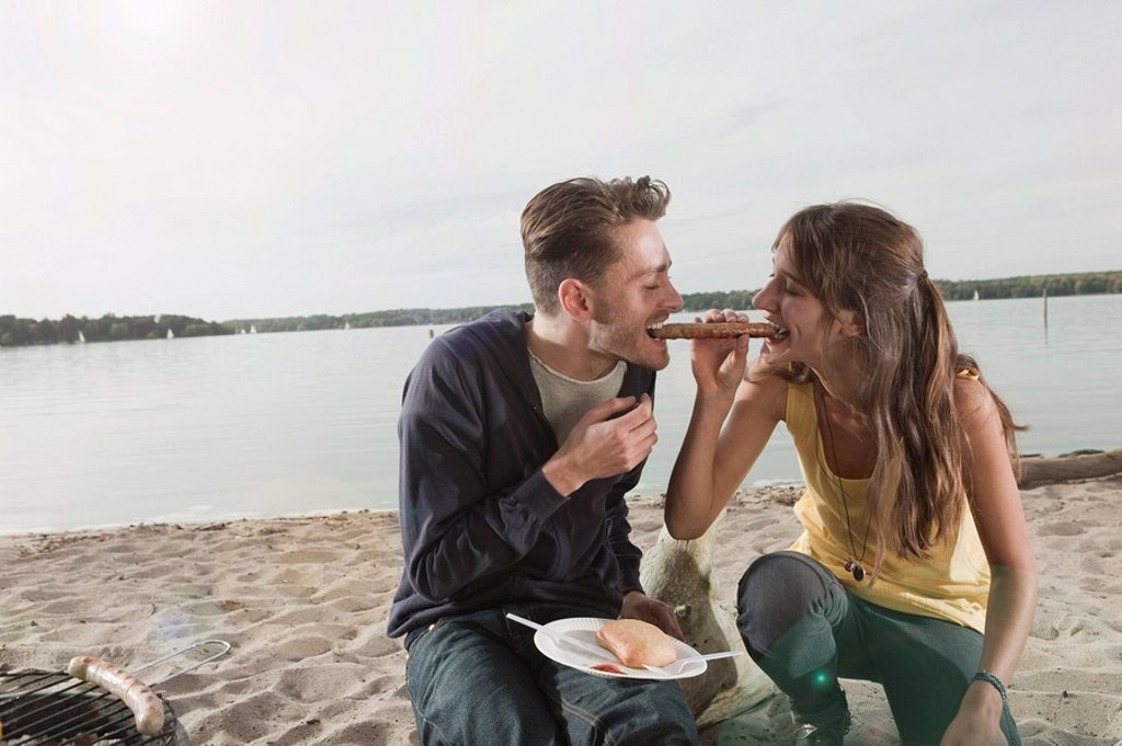 Germany, Berlin, Lake Wannsee, Young couple having a barbecue : Stock Photo