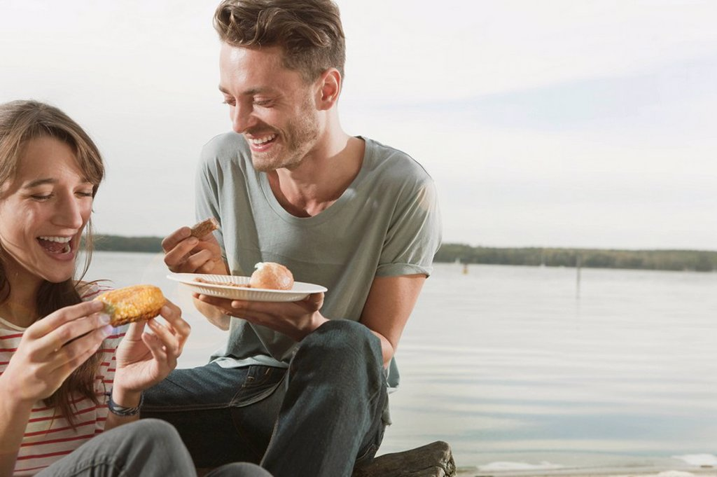 Germany, Berlin, Lake Wannsee, Young couple having corn and sausage : Stock Photo