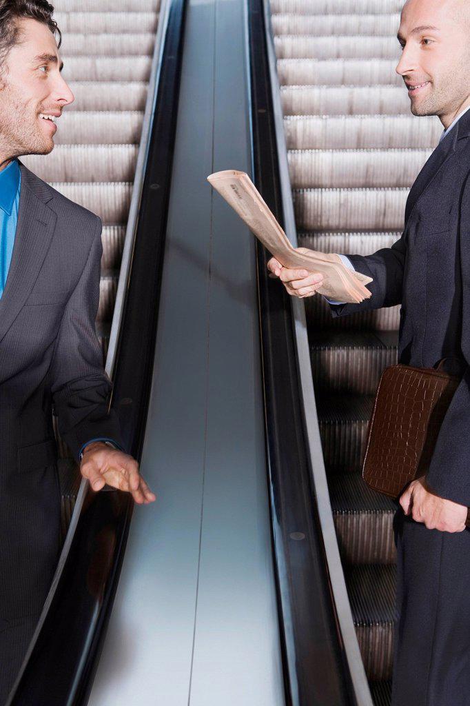 Germany, Bavaria, Munich, Two businessmen on escalator : Stock Photo