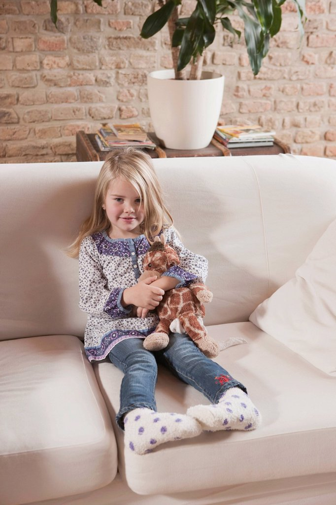 Germany, Cologne, Girl 4_5 with a stuffed toy, sitting on sofa : Stock Photo