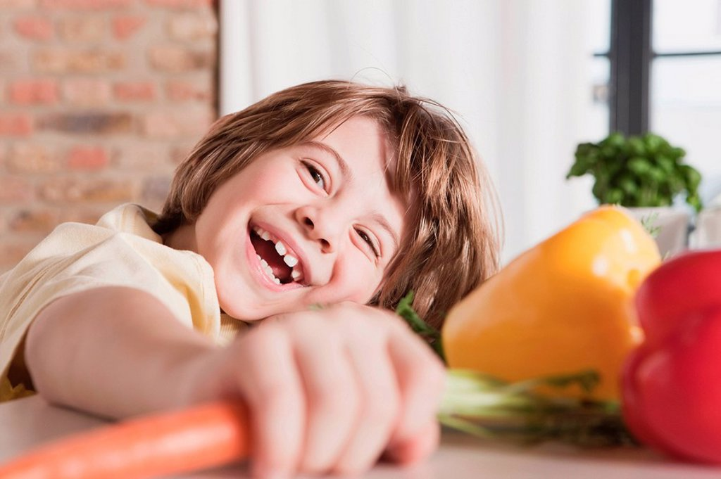 Germany, Cologne, Boy 6_7 in kitchen holding carrot, laughing, portrait, close_up : Stock Photo