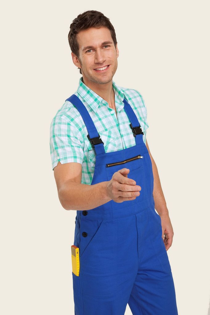 Man in overall smiling, portrait : Stock Photo