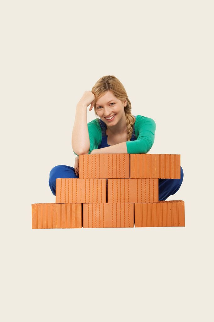 Stock Photo: 1815R-66644 Woman sitting behind stack of bricks, smiling, portrait