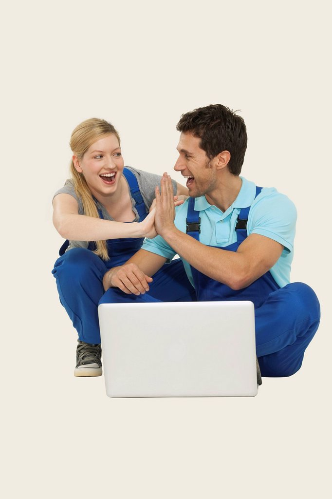 Man and woman in overall using laptop, giving high_five : Stock Photo
