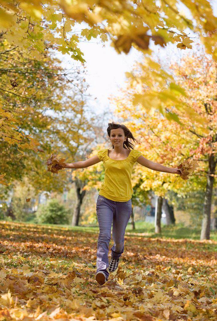Austria, Female teenager 14_15, running across park, having fun : Stock Photo