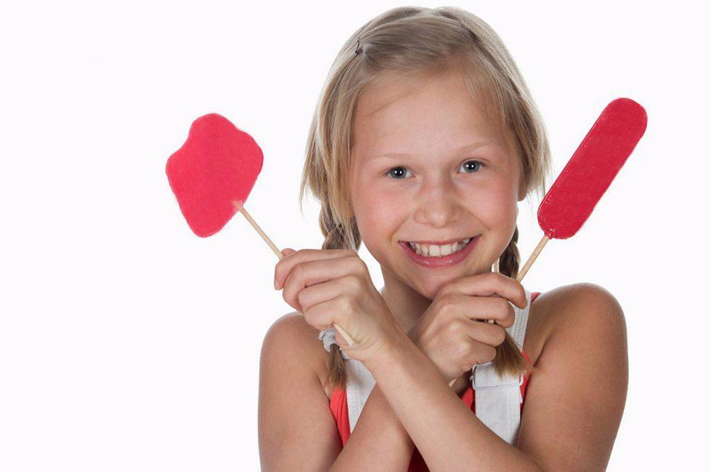 Girl 10_11 holding lollypops, smiling, portrait : Stock Photo