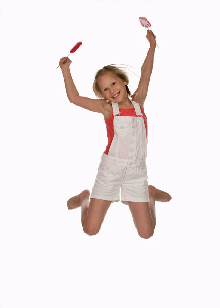 Girl 10_11 holding lollypops, jumping in air, smiling, portrait : Stock Photo