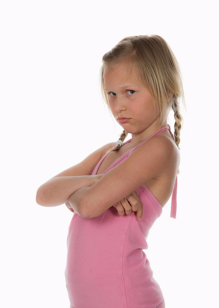 Portrait of a girl 10_11 arms crossed, pouting, side view : Stock Photo