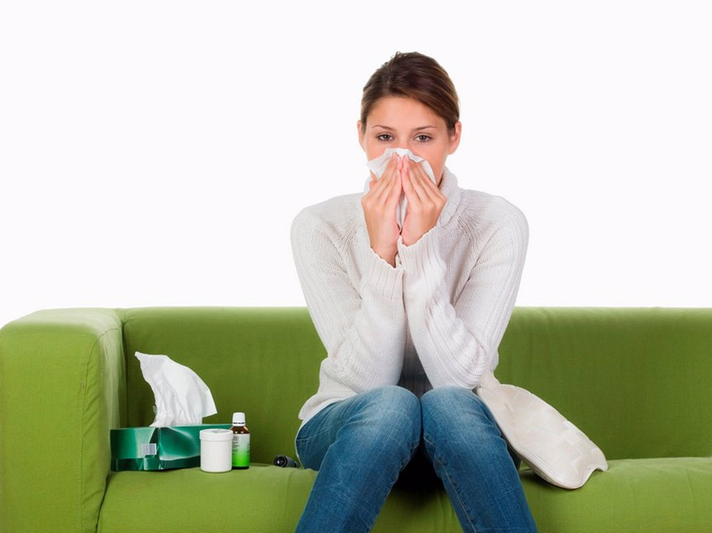 Young woman on sofa blowing nose : Stock Photo