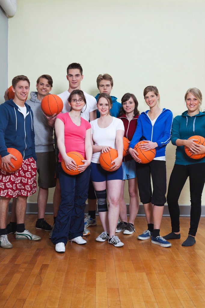 Germany, Berlin, People standing and holding basketball, portrait : Stock Photo