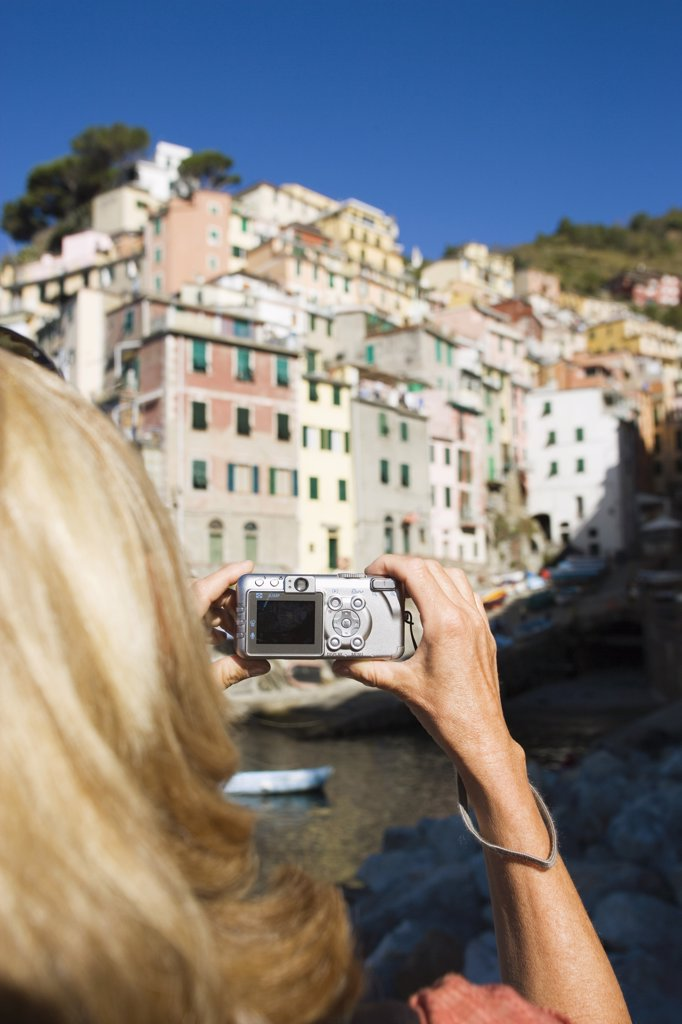 Stock Photo: 1815R-6757 Italy, Liguria, Riomaggiore, Woman photographing houses