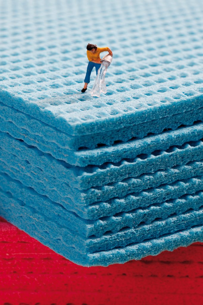 Woman figurine pouring water on sponge cloth : Stock Photo