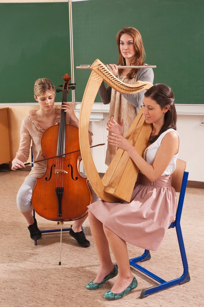 Germany, Emmering, Teenage girl and young women playing musical instruments : Stock Photo