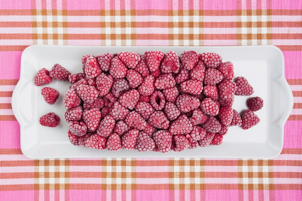 Frozen raspberry in tray on tablecloth : Stock Photo