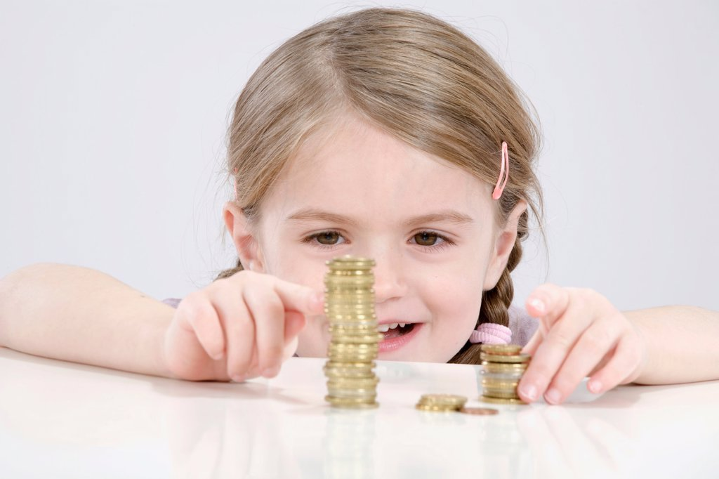 Girl 4_5 counting stack of coins : Stock Photo