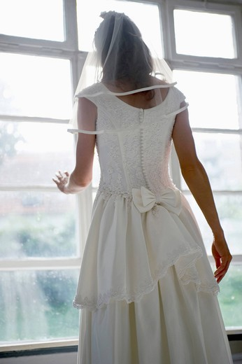 Bride looking through window, rear view : Stock Photo