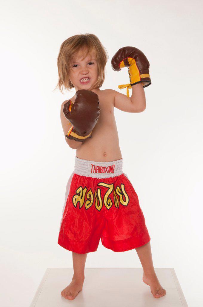 Boy 4_5 wearing boxing glove, clenching teeth : Stock Photo