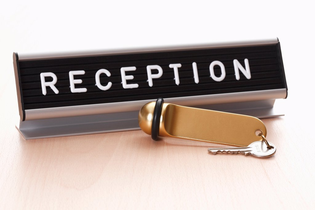 Reception sign with hotel key on desk : Stock Photo