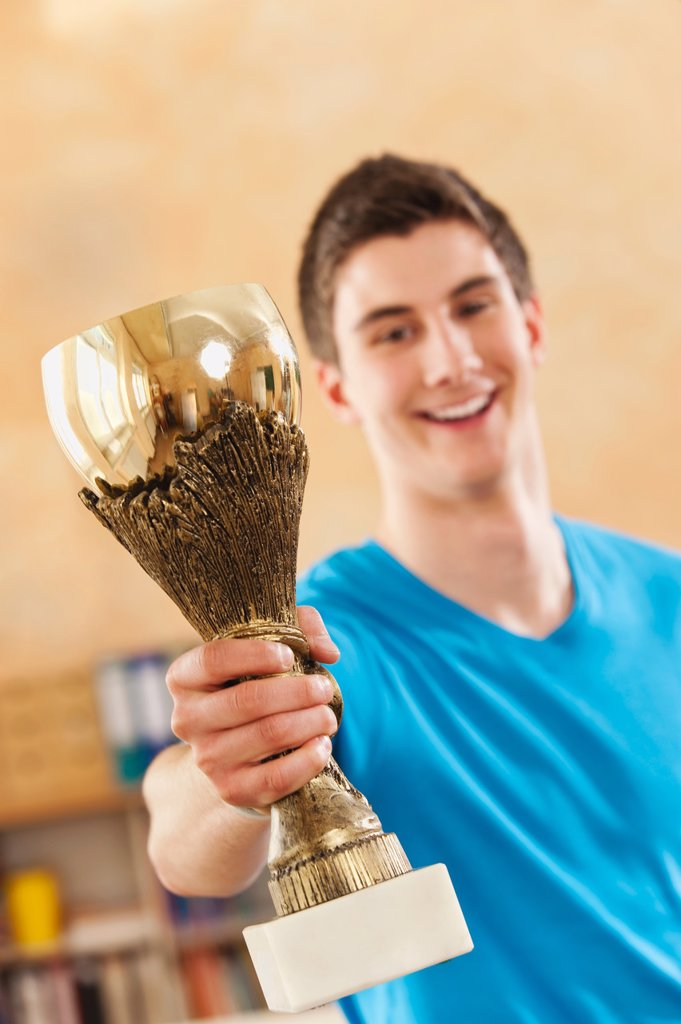 Germany, Emmering, Teenage boy holding trophy, smiling, portrait : Stock Photo