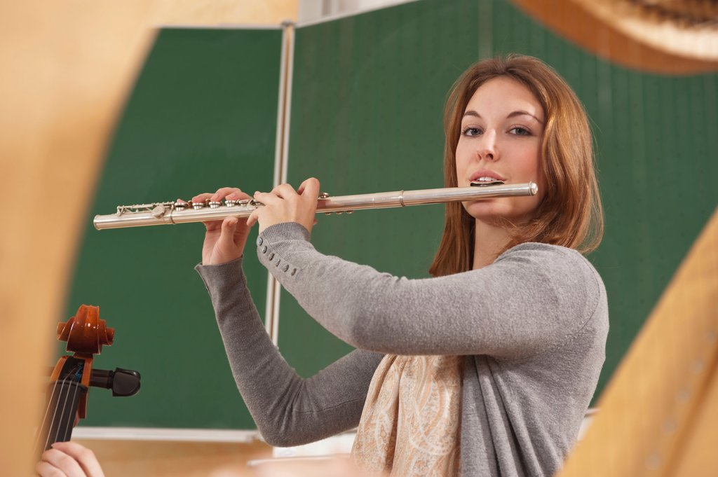 Germany, Emmering, Teenage girl blowing flute : Stock Photo