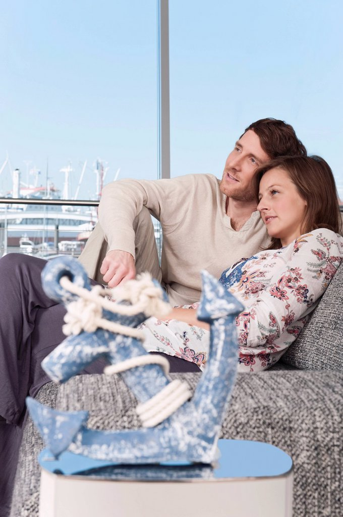 Stock Photo: 1815R-74336 Germany, Hamburg, Man and woman looking away and resting on couch