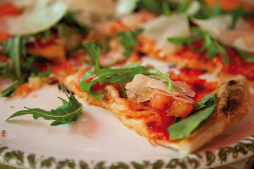 Pizza garnished with rocket, tomatoes and parmesan, close up : Stock Photo