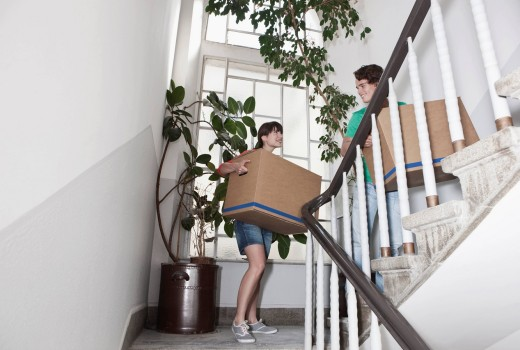 Stock Photo: 1815R-76926 Germany, Cologne, Young couple carrying carton on stairway in renovating apartment