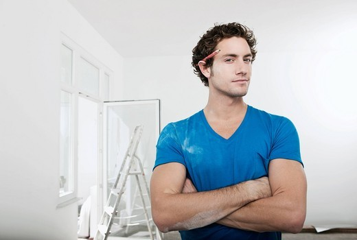 Stock Photo: 1815R-76966 Germany, Cologne, Young man with pencil behind ear in renovating apartment, portrait