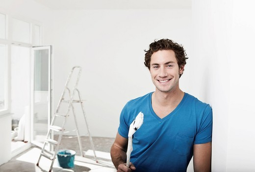 Germany, Cologne, Close up of young man holding paint brush in renovating apartment, smiling, portrait : Stock Photo